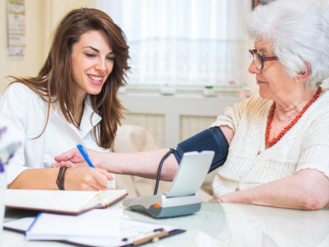 skilled nurse checking senior womans blood pressure