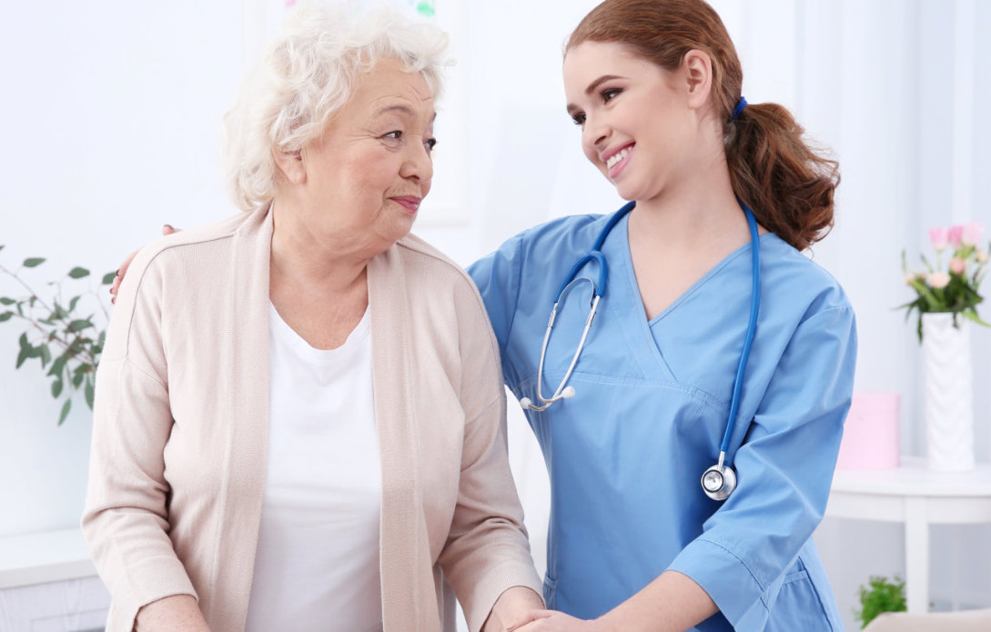 female nurse smiling at senior woman
