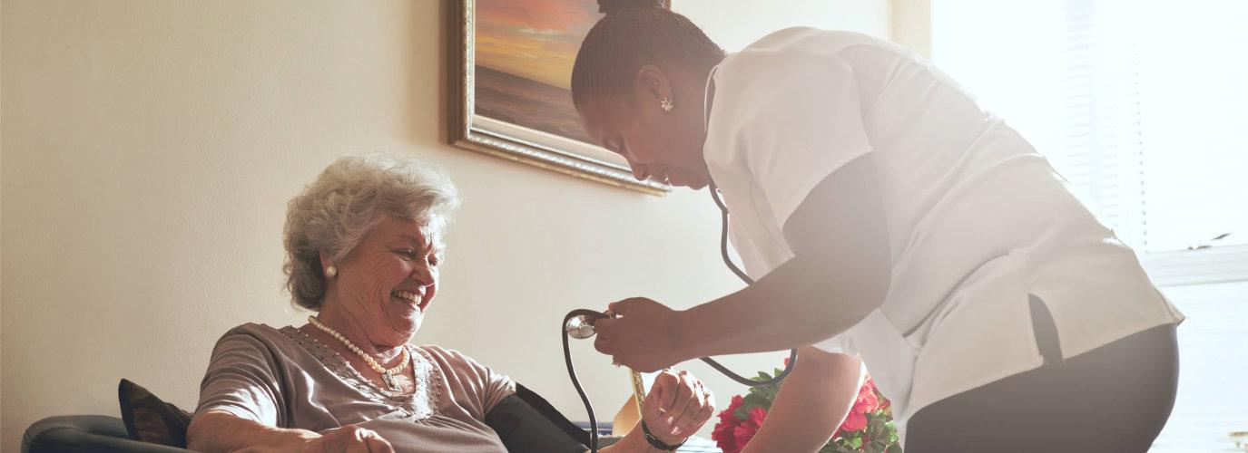 nurse checking senior womans blood pressure