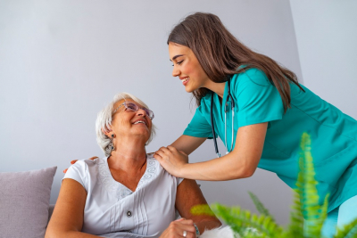 skilled nurse looking at the senior woman while smiling