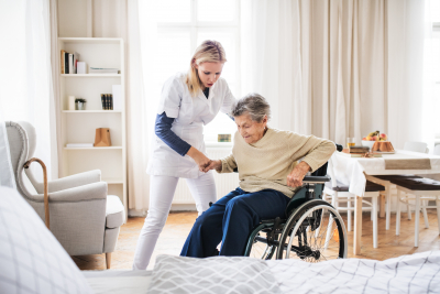 caregiver assisting senior woman to stand and walk