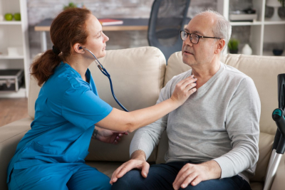 nurse checking senior mans breathing