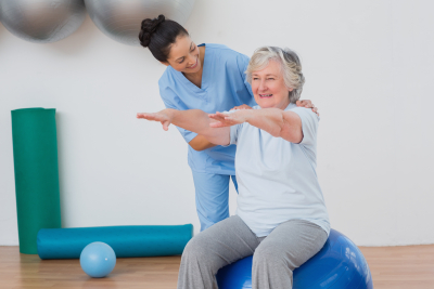 caregiver assisting senior woman in physical activity